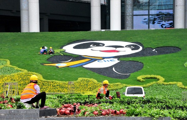 Gardeners trim a lawn featuring the image of Jinbao, the mascot of the China International Import Expo, at the National Exhibition and Convention Center in Shanghai on Oct 15. [Photo by Yang Jianzheng/For China Daily]