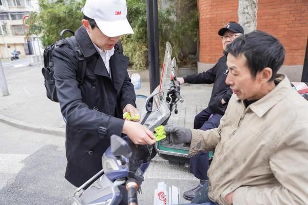 3M志愿者向过路的非机动车驾驶员赠送骑行反光贴