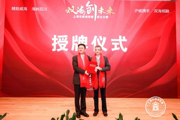 上海市人民政府合作交流办公室副主任熊英为上海市威海商会名誉会长徐曙光授牌。
