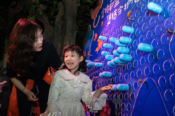 游客参与时光胶囊互动、插入时光胶囊的鲨鱼主题板
