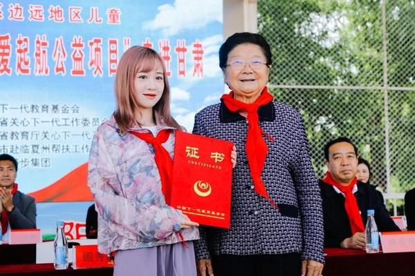 特步集团公益推广大使丁佳敏接受顾委员长颁发证书