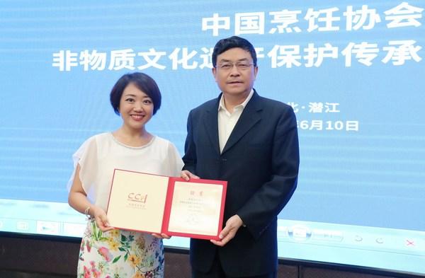 中国烹饪协会会长傅龙成向李锦记中国企业事务总监陈姝(左)颁发副主任单位证书