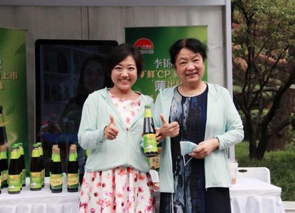 李锦记酱料集团中国区企业事务总监陈姝(左)向中国食品科学技术学会孟素荷理事长介绍本次展出的新品