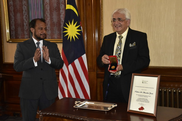 Prof. Sir Alimuddin Zumla (right) receives the 2020 Mahathir Science Award from Mr. Zahid Rastam (left), Chargé d'Affaires at the Malaysian High Commission in London.