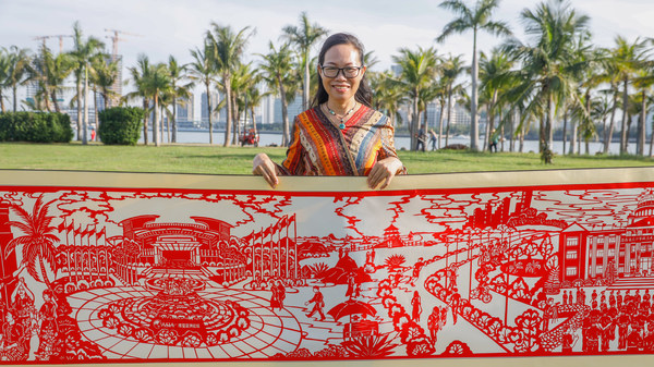 Huang Haitao, who led the papercut team, shows the part of the 22-meter scroll depicting the Boao Forum for Asia conference. (Photo/HIMC)