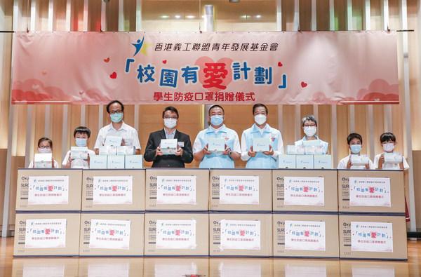香港義工聯盟青年發展基金會主席馬少福(左五)向中華基督教會協和小學(長沙灣)全校同學送贈防疫口罩,並由蔡世鴻校長(左四)、陳國源副校長(左三)及學生代表接收。
